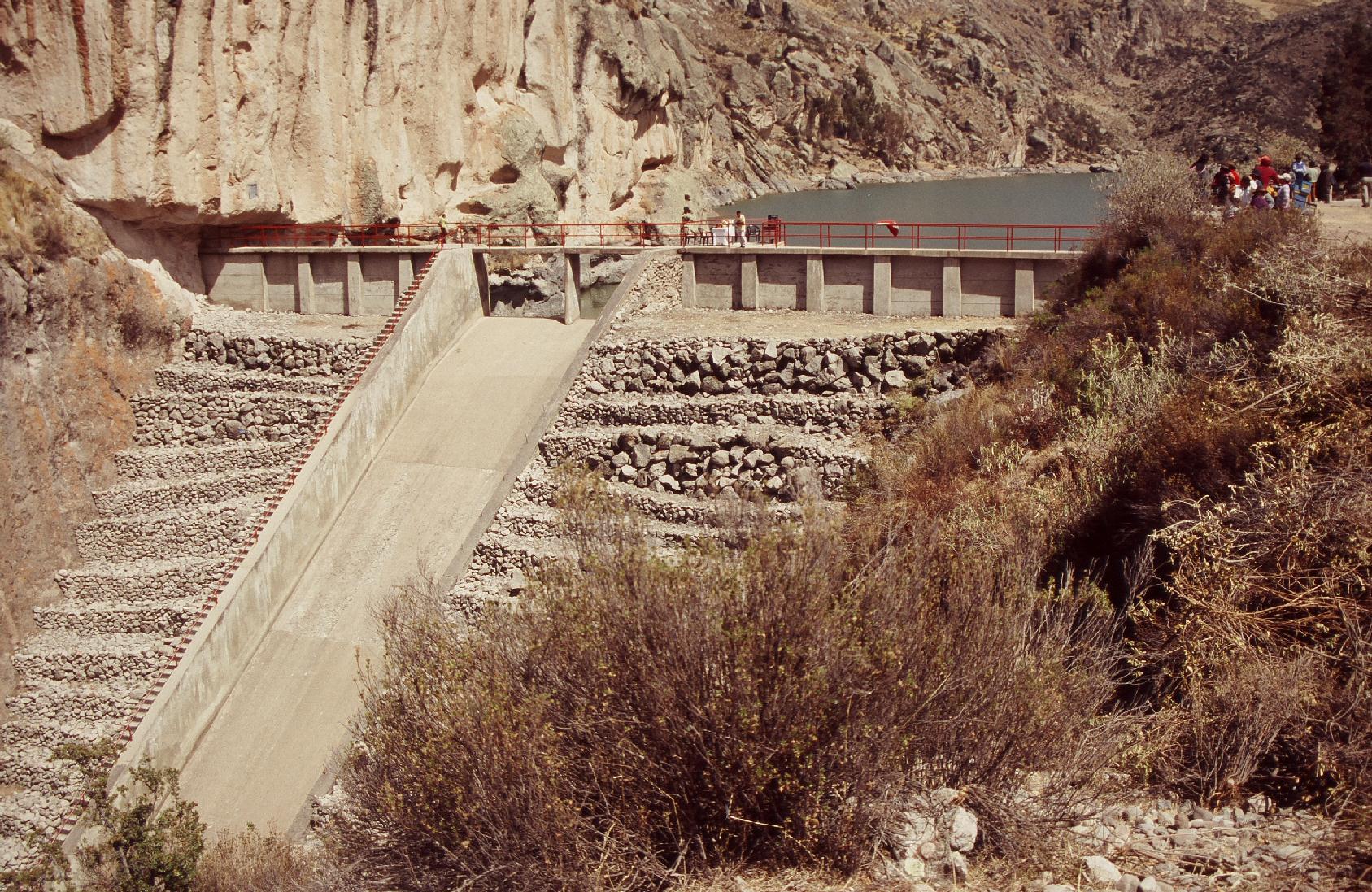 Luftseite des Staudamms mit Hochwasserüberlauf bei gefüllter Talsperre